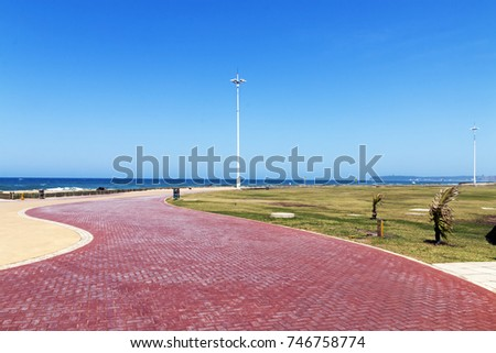 Empty red paved promenade pattern and texture against sea and blue sky at Blue Lagoon in Durban, South Africa