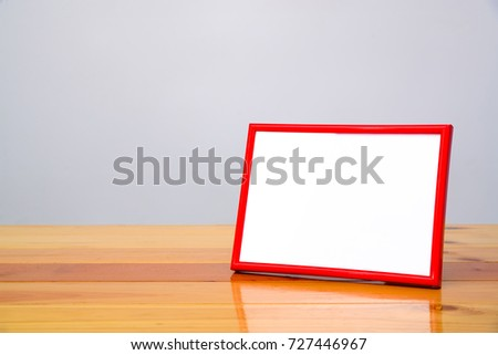 Empty red photo frame on bright wooden table with copy space, picture memory.