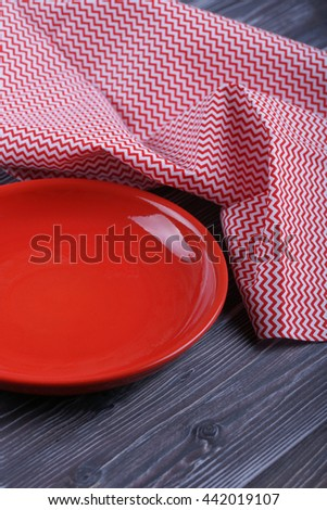 Empty red plate on a wooden table
