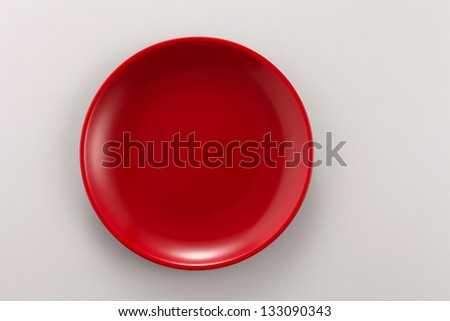 Empty red plate on the white background