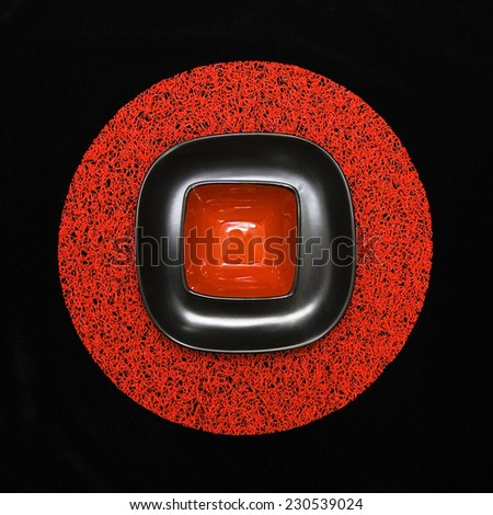 Empty red square red bowl on a black plate on red placemat over black background - stock photo