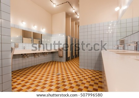 Empty restroom with washbasin and separated toilet cabins in a modern youth hostel