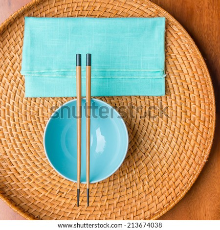 Empty rice bowl with bamboo chopsticks on wooden wickered  tray. - stock photo