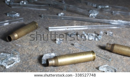 Empty rifle casings that are surrounded by glass on concrete - stock photo