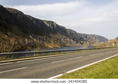 Empty road beside a lake in the Isle of Skye in Scotland - stock photo