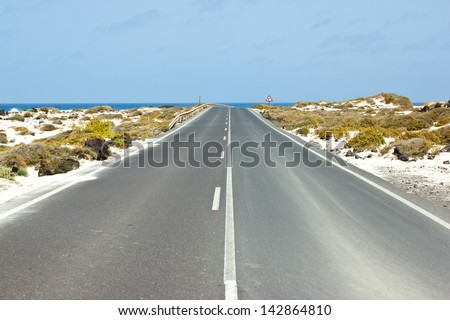 Empty road between mountains leading to the sea, Canary islands, Spain - stock photo