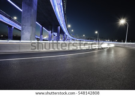 Empty road floor with city overpass viaduct bridge of neon lights night scene