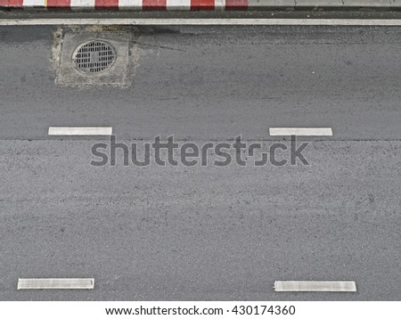 Empty road from top view, asphalt texture with red and white road sign and metal cover the drain on road. - stock photo