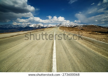 Empty road going to a mountain range under blue sky with fluffy clouds - stock photo