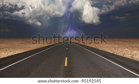 Empty road in desert storm - stock photo