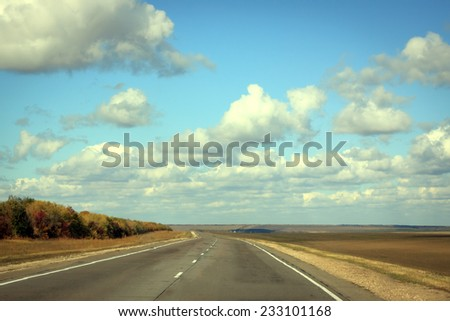 Empty road in sunny autumn day with cloud on the blue sky - stock photo
