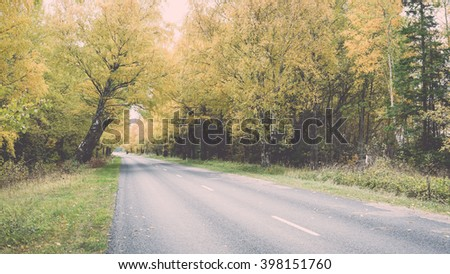 empty road in the countryside with trees in surrounding. perspective in autumn - vintage film effect