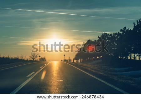 Empty road leading to sunset. - stock photo