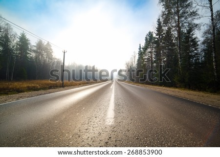 Empty road stretching out into the distance - stock photo