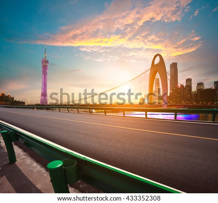 Empty road surface floor with modern city landmark architecture backgrounds of pink clouds in Guangzhou China - stock photo