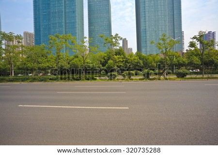 Empty road surface with modern city buildings background - stock photo