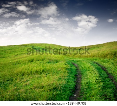 empty  road through fields with green grass and blue sky with clouds, natural background