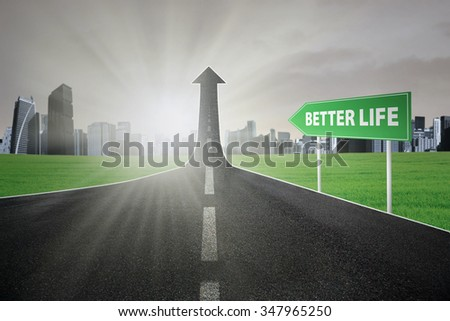 Empty road with better life text on signboard turning into arrow upward, symbolizing the way toward better life