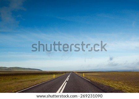 Empty road with blue sky in wild Iceland