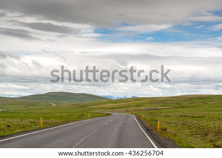 Empty road with cloudy skies in wild Iceland - stock photo