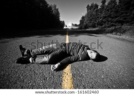 Empty Road With Dead Body in the Middle At Night - stock photo