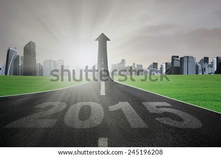 Empty road with number 2015 turning into arrow upward, symbolizing the way toward 2015 - stock photo