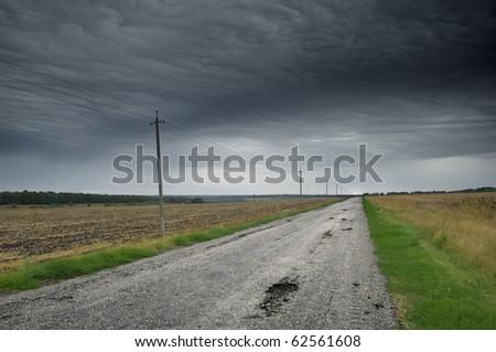 Empty road with thunderclouds on background