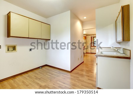 Empty room with a washbasin cabinet and wall cabinets.