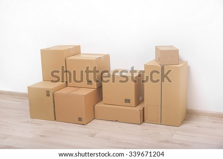 Empty room with a white wall and cardboard boxes with unbranded barcode on the floor.