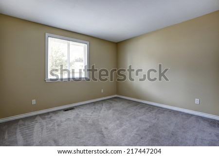 Empty room with grey carpet floor and window.