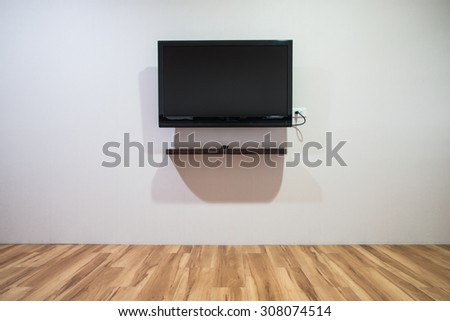 Empty room with HD TV at the wall - stock photo