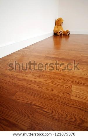 Empty room with teddy bear in corner - stock photo