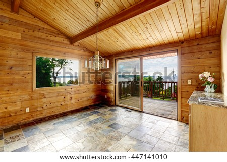 Empty room with tile floor and wooden trim. Opened balcony door. Way to deck and patio area with water view - stock photo