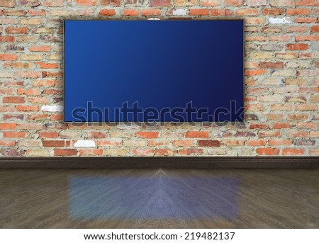 Empty room with tv on brick wall.