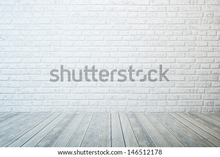 empty room with white brick wall and wooden floor - stock photo