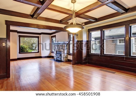 Empty room with wood paneled walls and coffered ceiling.  View of family room with old fireplace with stone trim.  Northwest, USA
