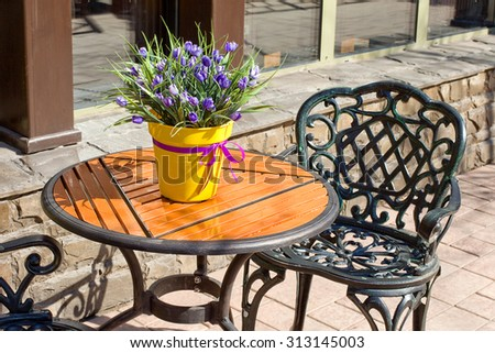 Empty round wood table top with vases of flowers and chairs at coffee shop on the street. ,Template mock up for display of your product
