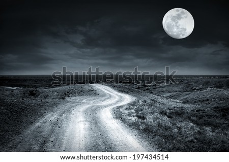 Empty rural road going through prairie at full moon night with dramatic cloudy sky - stock photo