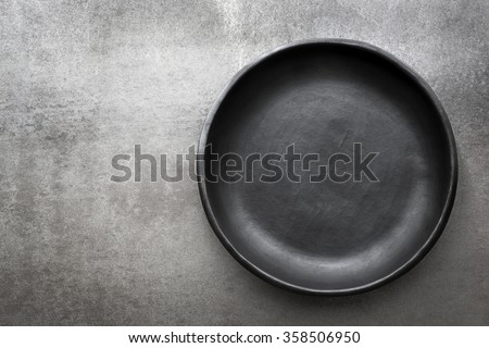 Empty rustic black plate over gray slate.  Aerial view, with copy space. - stock photo