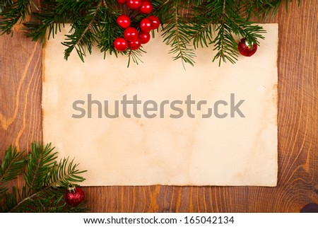 Empty rustic paper with juniper leaves and Christmas globes around, wooden background  - stock photo