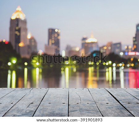 empty rustic wooden table and with blurring lights of cityscape background, for product display