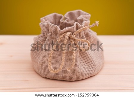 Empty sack on a wooden surface over dark yellow background - stock photo