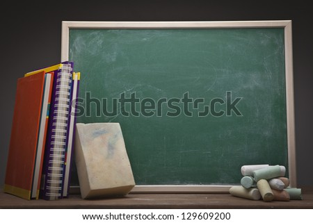 Empty school blackboard with books and sponge - stock photo