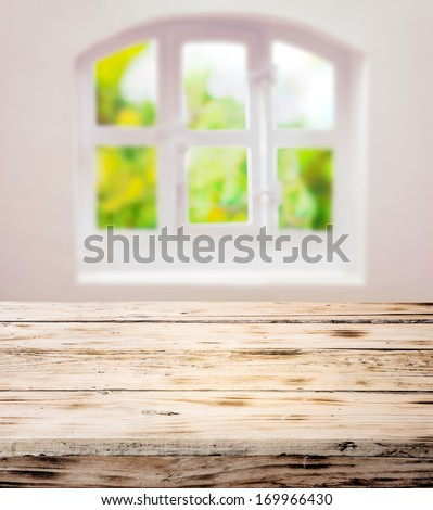 Empty scrubbed clean rustic wooden kitchen table under a pretty white domed window with cottage panes in a country kitchen ready for your cooking ingredients or product placement - stock photo