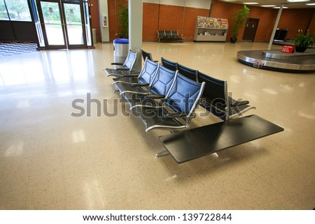 Empty seats and luggage belt at an airport