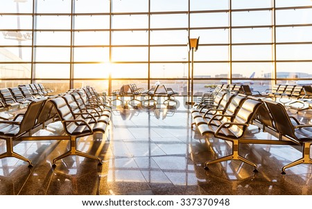 Empty seats in the departure lounge at the airport in the sunset - stock photo