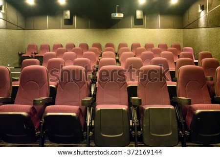 Empty seats in the small movie theater with cinema projector - stock photo
