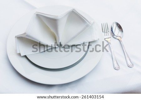 Empty served restaurant table with white tablecloth - stock photo