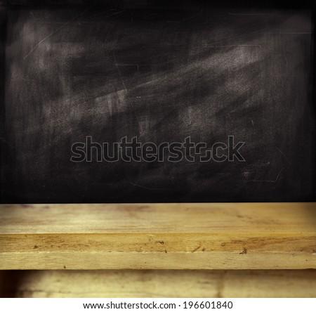 Empty shelf in front of blackboard - stock photo