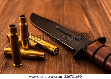 Empty shells from the rifle and combat knife lying on a wooden table. Focus on the shells - stock photo